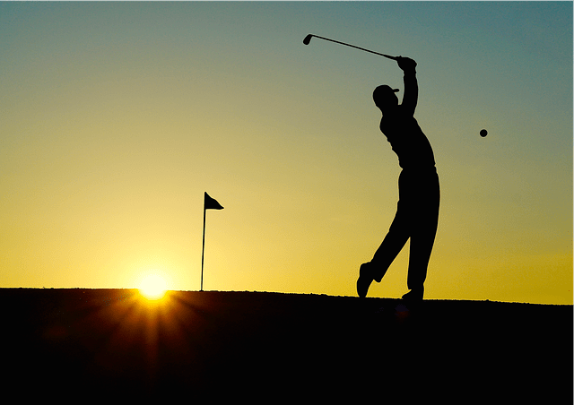 silhouette of a golf swing at sunset